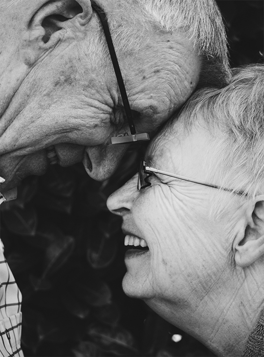 Two elderly people smiling at each other and bumping foreheads.